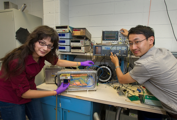 """Design Engineer Justine Haupt (left) and Postdoctoral Research Associate Dajun Huang (right) prepare a test chamber that scientists in the Instrumentation Division are are using to evaluate the digital sensors they are designing for the Large Synoptic Survey Telescope, which is scheduled to see """"first light"""" in 2020, and start surveying in 2022."""