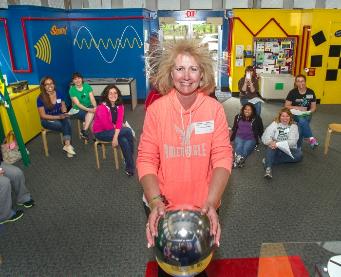 A Girl Scouts of Suffolk County staff member's hair stands on end as she places her hands on the Van de Graff generator, propelled by the power of static electricity. Charge builds up on the Van de Graff, and transfers to her hands when she places them on the generator. Once the electric charge courses through her body and reaches her hair, it makes the hair follicles repel one another since they reach the same potential, so they stand up. Using hands-on activities like this one, the GSSC staff will teach the girl scouts about the science they learned at Brookhaven National Laboratory workshops.